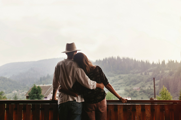virgo-man-and-virgo-woman-hugging-on-porch-of-wooden-house-looking-at-mountains-in-evening-sunset
