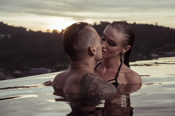 Romantic sensual couple alone in infinity swimming pool over beautiful tropical and sunset sky - what virgo man likes in bed