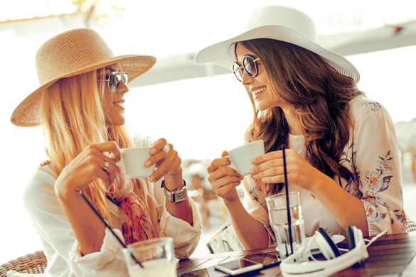 women-holding-coffee-cup-while-looking-at-each-other-in-cafe-what-a-virgo-man-likes-in-a-women