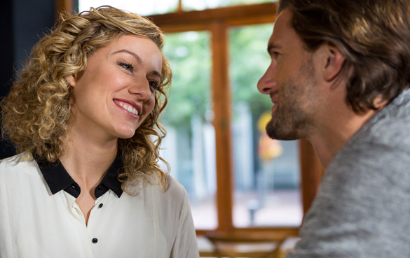 Smiling woman talking with man in coffee shop - Why Does A Virgo Man Ask So Many Questions All The Time
