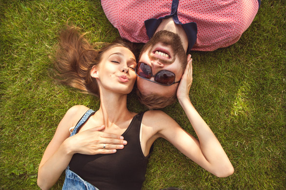 couple in love in sunglasses lying on the grass and laugh - What is the Best Way to Date a Virgo Man