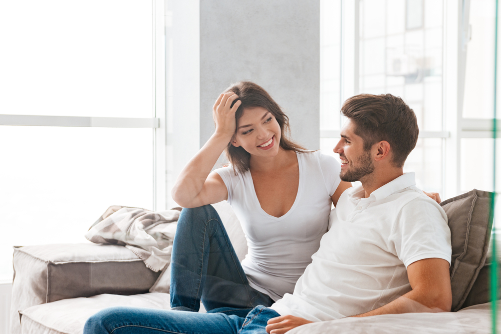 Cheerful beautiful young couple sitting and talking on sofa at home - Virgo Man Cancer Woman Problems